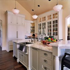 Traditional Kitchen with Carrera marble countertop, Farmhouse sink, Raised panel, Glass panel, Breakfast bar, Hardwood floors