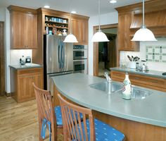 A kitchen remodel with maple cabinets, soft green Corian countertops and hardwood floors.