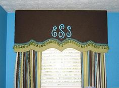 Do a monogrammed cornice, and then add two shower curtains???? Monogrammed, tassel embellished, banded cornice