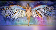 MillieNewitt Public art piece titled Wings to Fly. Located on The Strand, Tauranga, New Zealand. This interactive mural invites the viewer to stand in the middle of the angel wings to have their photograph taken.