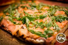 Pizza with Salmon and rocket salad. It has the same dough of the white one, but it is spiced with raw tomatoes, salmon and rocket salad