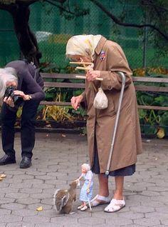 Una ardilla siendo alimentada por una marioneta que representa a la anciana dama que maneja a la marioneta.