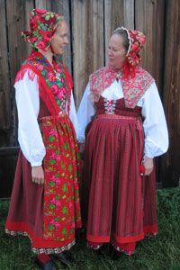 """Kvinnodräkter från Nås i Dalarna. T.v. högtidsdräkt med hätta, krage och förkläde av blommigt yllemuslin. T.h. enklare dräkt med förkläde av halvylletyg och krage av kattun. Kjolarna kantas av den s.k. """"virkflätan"""" – ett flerfärgsvirkat band."""