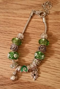 Bracelet wide hole beads in green and silver with silver tone charms
