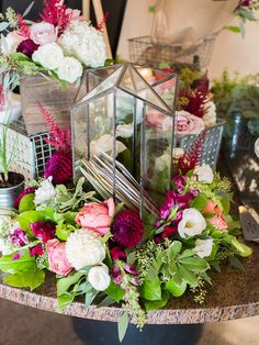 Clear glass card box nestled within greenery and flowers.   A Modern Wedding At The National Gallery Of Canada | Weddingbells