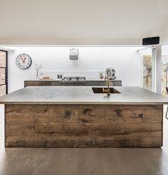 Bespoke reclaimed cladding kitchen island. All about the materials. Woods, concrete and brass finishes.