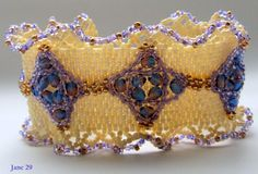 Bead woven Creamy Eggshell Seed Beads and Adorned with Purple and Gold Bead done in a Peyote Stitch Bracelet