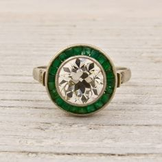 love the emeralds around the  diamond