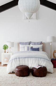Chic bedroom design by Cupcakes and Cashmere. Love the white walls, exposed beams and bright light fixtures. Add poufs at the foot of the bed instead of a bench for a more boho look. Pillow shams and bedding is pure cotton and has a subtle geometric indigo pattern. #nordstrom @nordstrom