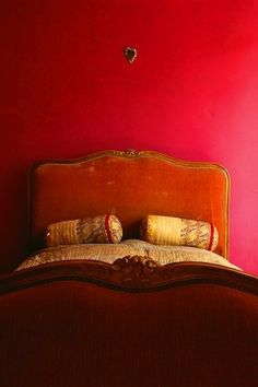 Saturated color, deep pinky red walls, rusty orange velvet antique bed head dressed with Indian pillow rolls. Charming bedroom bohemian eclectic, pink or red? Bedroom Red, Home Bedroom, Fuschia Bedroom, Bedroom Colors, Bedroom Decor, Trendy Bedroom, Bedroom Vintage, Et Wallpaper, Indian Pillows