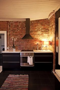 Modern meets brick kitchen plus black cabinets plus white wood ceiling. Yes please.