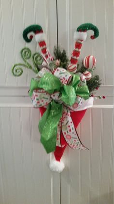 Best 11 A whimsical decoration perfect for a wall or door. This Santa hat is filled with a variety of greens, colorful ribbon and cute elf feet! May vary slightly from picture. Christmas Swags, Christmas Door Decorations, Grinch Christmas, Christmas Centerpieces, Rustic Christmas, Christmas Ornaments, Christmas Time, Xmas Wreaths, Christmas Lanterns