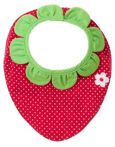 Fresh strawberry style for snack time! Allover mini dot print with a little blossom appliqué on one side of our soft cotton interlock bib, and coordinating strawberry print on the reverse. Finished with darling leaf shaped ruffles around the neck.