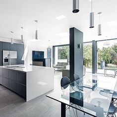 Open-plan kitchen with grey handless cabinetry, glass dining table and black leather and chrome chairs