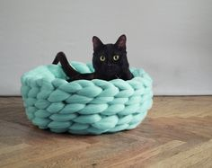 Anna Mo (previously) knits with chunky spools of wool, utilizing giant needles to produces the three-inch stitches that comprise her blankets, wraps, and now tiny pet beds.