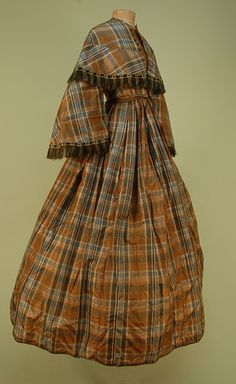 TARTAN SILK DRESS, 1850's. 2-piece blue, black, cream and mocha taffeta, boned high neck collarless bodice with striped fringed pagoda sleeve and flounce, five faux dorset buttons, front hook & eye closure, full skirt with waist pleats, braided hem binding, all lined in fawn cotton twill. Bust 34, waist 26, skirt length 43 1/2.