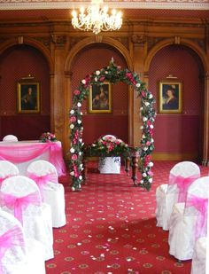 Pretty in pink in The Grand Ballroom, Haigh Hall.  Our white chair covers dress the chairs along with a hot pink sash.  The bridal arch is co ordinated in hot pink and white flowers.  www.am-flowers.co.uk