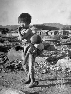 Girl Standing in Rubble from the Korean Civil War, Carrying a Baby in a Sling on Her Back Premium Photographic Print by Joe Scherschel at Art.com