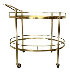 "A timeless oval two-tiered solid brass bar cart by Maxwell Phillips. Sleek, sturdy, and elegant. Casters are in brass too. High quality. Height is with the handle. The height without the handle is 27. Top shelf is 25"" in height and the bottom shelf is 10"" in height. Very light patina, few micro chips on glass shelves."