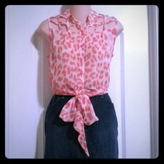 Trendy tie-front caged sleeveless top! This top is very unique. It is a size large by Poof Couture and it is a pink/peach color with dark pink print. The top part is caged and very unique. It has a long tail down the back that can be tucked in. **Host Pick 7/26 Off-Duty Chic Party!** Poof Couture Tops