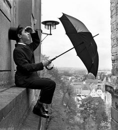 I hope he doesn't think that umbrella will soften his fall if he slips off that ledge.