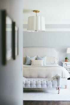 Ivory and blue bedroom features tray ceiling accented with Barbara Barry Simple Scallop Pendant over blue walls framing a ivory linen bed with nailhead trim dressed in ivory and blue bedding beside mirrored nightstands topped with Anita Table Lamp alongside a tufted bench on caster legs placed at the foot of the bed atop a white rug layered over oak hardwood floors.