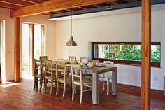 Velký jídelní stůl obklopují židle nakoupené ve vetešnictví.
