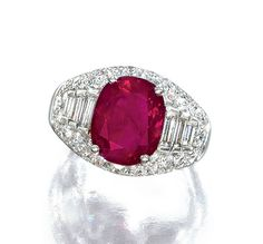 RUBY AND DIAMOND RING, BULGARI. Set with a cushion-shaped ruby weighing 5.06 carats, the bombé mount partly pavé-set with brilliant-cut diamonds, and decorated with baguette diamond shoulders, mounted in platinum, signed Bulgari.