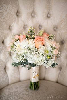 Vintage garden bouquet with soft white hydrangea, roses, mums, and peach spray and standard roses, accented by September and gypsophila and a heirloom brooch. Image by KWP Weaver