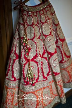 Bridal Lehenga - Raw Silk Red and Orange Lehenga with Silver Embroidered Motifs and Red and Gld Pom-Poms | WedMeGood  Picture Courtesy : Shweta Poddar Photgraphy #wedmegood #indianwedding #indianbride #lehenga #rawsilk #red #orange