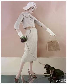 1957 Jessica Ford in oatmeal colored rayon-tweed suit with short jacket over straight skirt belted in tan calf leather, photo by Karen Radkai, Vogue