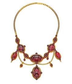 GOLD AND GARNET NECKLACE.  The swag-style necklace set with numerous oval and round cabochon garnets ranging in size from approximately 26.0 by 17.5 mm to 4.0 by 4.0 mm, gross weight approximately 43 dwts, length 15 inches, circa 1870.