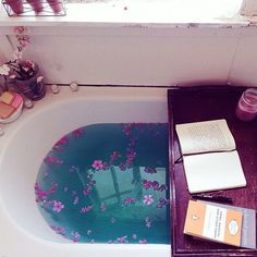 Bath with flower petals and entertainment. <3 LOVE the focus on purple. Water is such a pretty blue! Lush bath bomb?!