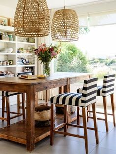 In the kitchen of this Buenos Aires home graphic striped fabric on the chairs balance the rustic nature of the table. Large overhead lighting adds drama and texture to the space.