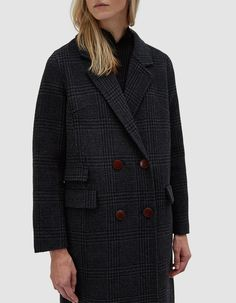 Classic overcoat from Ganni in Ebony Melange. Allover plaid. Notch lapel. Double breasted. Button closure. Front flap pockets. Back vent. Unlined. • Melton Wool • 70% wool, 30% polyamide • Dry clean