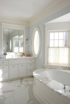 Elegant white and blue master bathroom features a wainscot oval drop-in bathtub fitted with a marble deck positioned beneath a bay window dressed in cream cafe curtains.