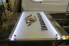 Frosted acrylic panels, with raised letters. Letters with brushed and polished metal laminate. Brushed stainless steel stand offs. White LED's assembled to back of panel for backlighting. impactsigns.com