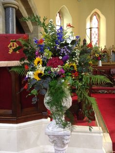 Bright wildflower urn arrangement by The Posy Barn