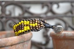 ett armband i brons o gult knutits på läderband..