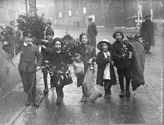 1915: Children carrying holly and mistletoe