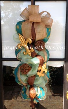 Door Swag/wreath in turquoise with burlap ribbon/ bow, peacock ribbon, and fleur de lis