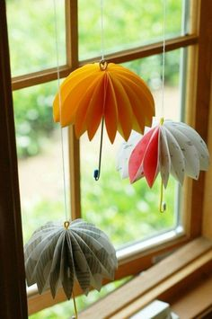summer craft ideas, three multicolored folded paper umbrella decorations, with wire handles, hanging from window pane, on white thread