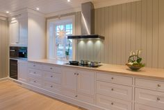 Hand painted white kitchen in solid pine from Os Trekultur. Worktop in stained and varnished oak. Integrated appliances and good storage solutions. Cabinet for oven, steamer and a wine fridge. Modern solution without cabinets above worktop.