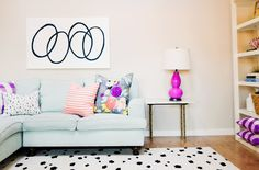 Pale blue sofa with lots of pink accents and black and white carpet and art