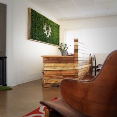 A glimpse of our reclaimed wood reception desk and framed topiary wall.