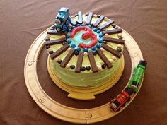Thomas the Train cake! Copied from other Pinners. Tracks are KitKats. Blue, tan, and brown stones are Almond Joy Pieces. Super easy!!!
