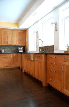 Cherry cabinets / black countertops / stone (?) backsplash / sleek hardware