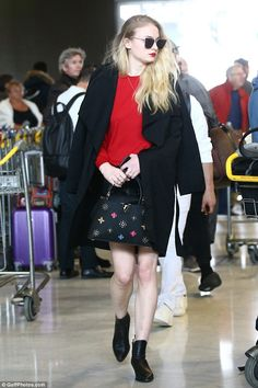 Looking glam: Opting for a red knit jumper to showcase her blonde tresses, Sophie kept warm with an oversized black coat draped over her shoulders