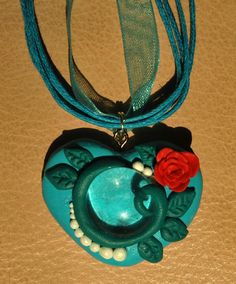 Pendant for Craftster challenge Nro 66. Made of polymer clay and glass bead.
