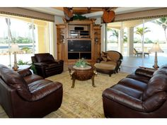 Great use of a corner entertainment center to allow view of pool and golf course at this West Bay Club home in Estero, FL.